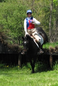 horse and riding landing from a jump while the rider smiles and waves